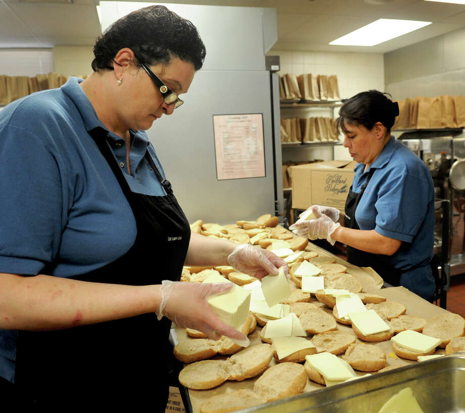 Ida Lopreiato, left, and Martha Pena, right, prepare bagged lunch at Westover Magnet Elementary School in Stamford on Tuesday, July 3, 2012, for students on the free- and reduced-price lunch plan at community organizations. Photo: Lindsay Niegelberg / Stamford Advocate