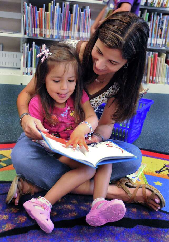 Marilyn Salazar, of The Woodlands, reads to her daughter, Valeria, in the children's section at the South Branch Library in The Woodlands. Photo: David Hopper / freelance