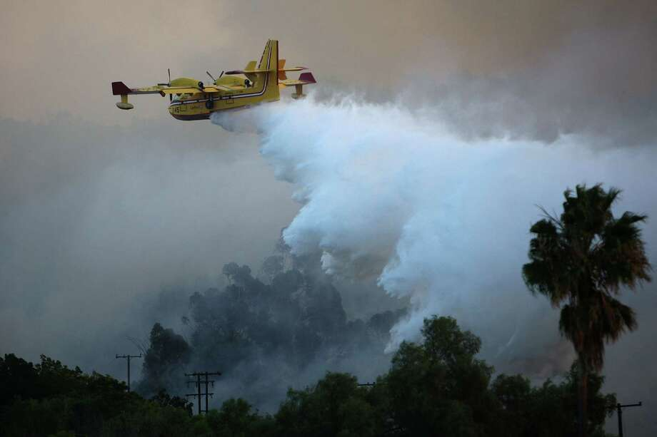 "Bombardier's 415 ""Superscooper"" firefighting tanker loads 1,621 gallons in 12 seconds while skimming at high speed over water. Here, a Superscooper drops water over the Brea Fire on November 15, 2008 near Yorba Linda, Calif. Photo: David McNew, Getty Images / 2008 Getty Images"