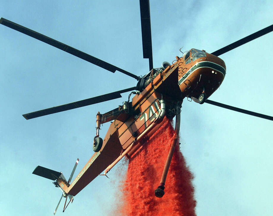 Similarly, the Erickson Aircrane helitanker can refill its 2,650-gallon tank using its snorkel in as little as as 45 seconds. This one is dropping fire retardant on July 14, 2004 near Three Points, east of Gorman, Calif. Photo: David McNew, Getty Images / 2004 Getty Images