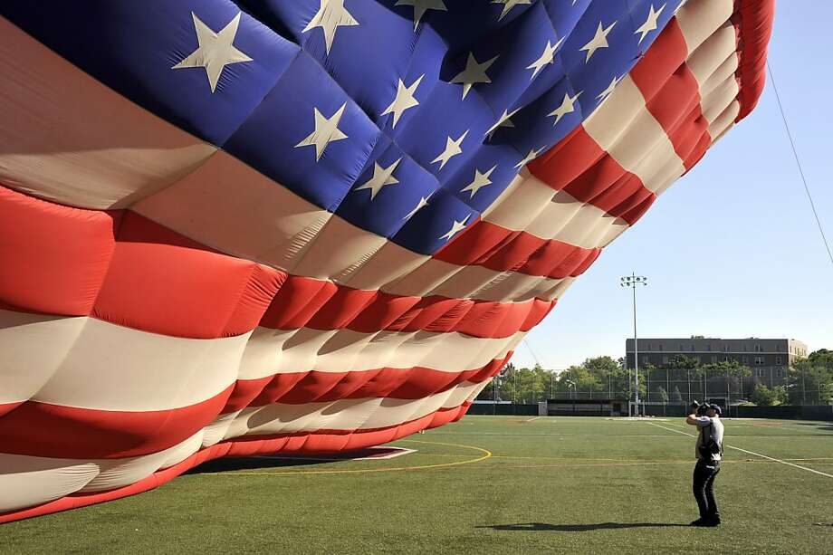 America the inflatable:A PNC American Flag balloon towers over a photographer at Stevens Institute of Technology in Hoboken, N.J. The hot-air flag will fly in honor of Independence Day. Photo: Michael Bocchieri, Getty Images