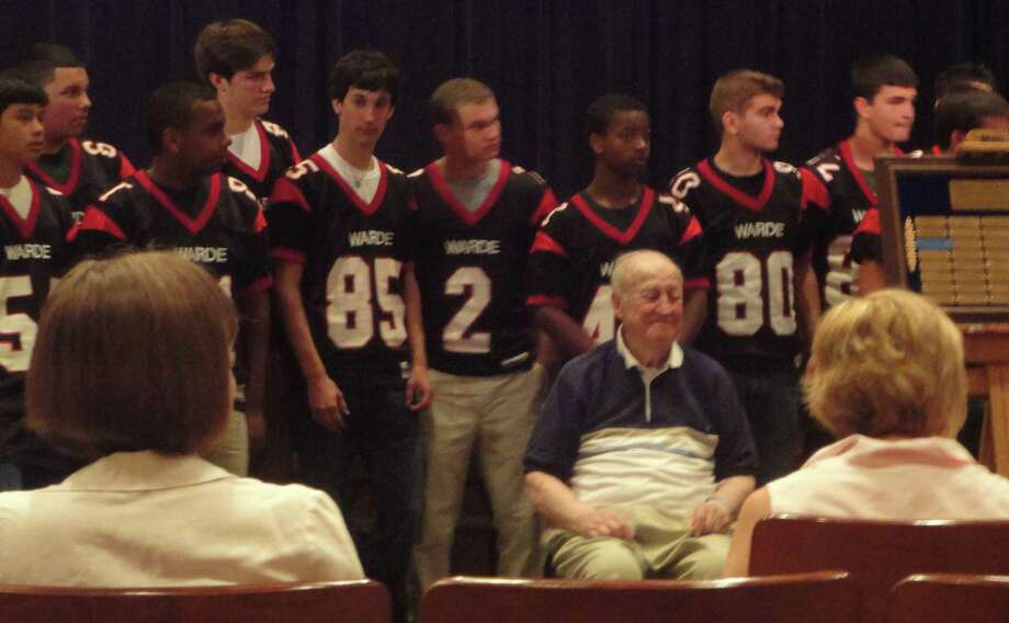 Fern Tetreau, the former football coach Roger Ludlowe and Andrew Warde high schools, is surrounded by current Warde players during ceremonies honoring him as a legend among Warde educators. Photo: Contributed Photo / Fairfield Citizen contributed