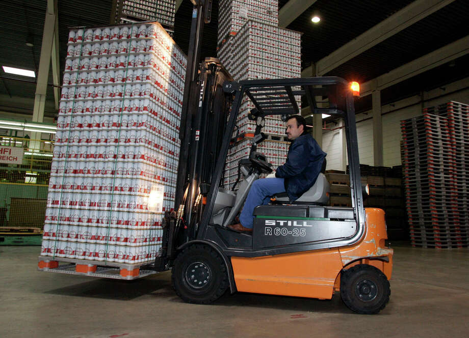 A worker uses a forklift to move cans at the Rexam factory in Berlin, Germany. Silgan Holidings Inc., Stamford-based producer of packaging products, will purchase Rexam's High Barrier Food packaging business for $250 million. Jochen Eckel/Bloomberg. Photo: Contributed Photo / Stamford Advocate Contributed