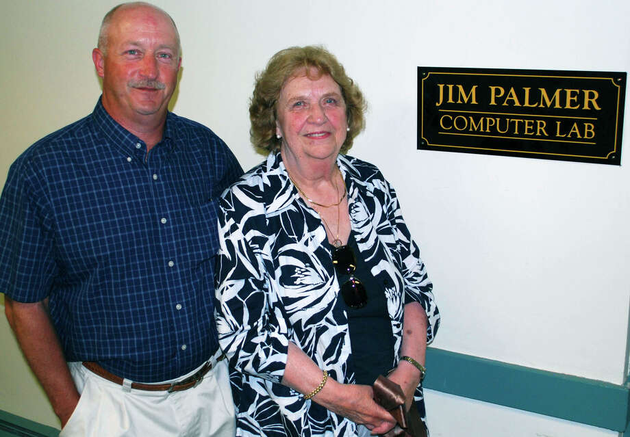 The computer lab at the New Milford Senior Center was recently named for the late Jim Palmer of Kent. A dedication ceremony was held June 21, 2012, at the center. Above, Mr. Palmerís wife, Doris, and his son, Scott, proudly stand beside the newly installed sign outside the lab.  Spectrum/After Cathy Setterlin of New Milford gets assistance with a spinning demonstration from Isabella Gimenez, Ms. Setterlin ties a woven bracelet onto the seven-year-old's wrist at Sunny Valley Preserve's Open Farm Day held Sept. 17, 2011 in New Milford. Photo: Deborah Rose