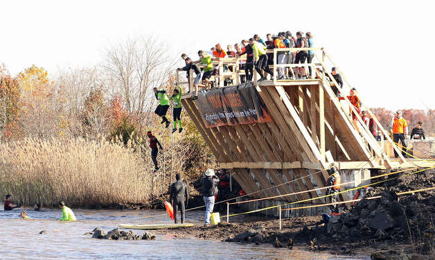 "Participants ""walk the plank"" in this part of the obstacle course of the ""Tough Mudder"" competition in New Jersey last year. Photo: Contributed Photo"