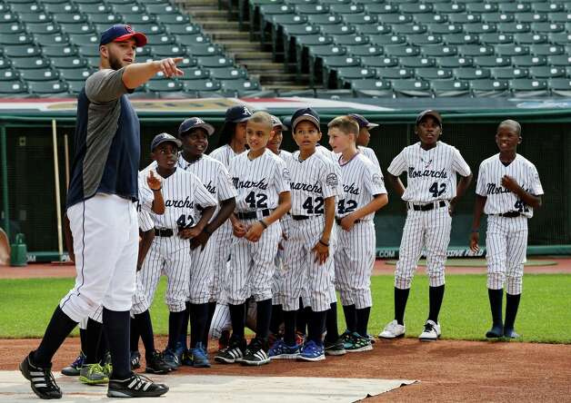 Indians starting pitcher Justin Masterson talks with the Monarchs youth team, which is on an 18-city tour aboard a 1947-era bus to pay tribute to the Negro Leagues. Photo: AP