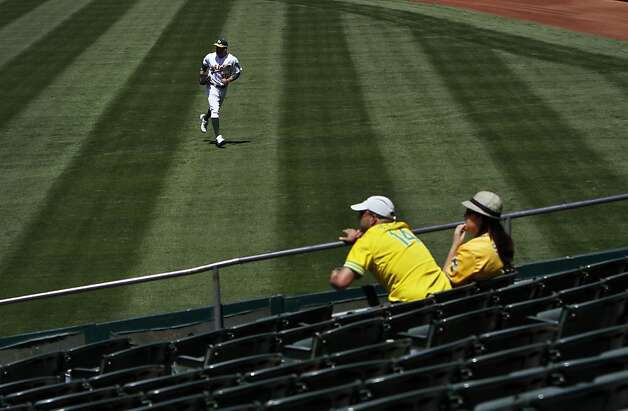 Oakland A's right fielder Seth Smith runs for the ball as a couple of fans watch during an Oakland home game in May. Photo: Sarah Rice, Special To The Chronicle