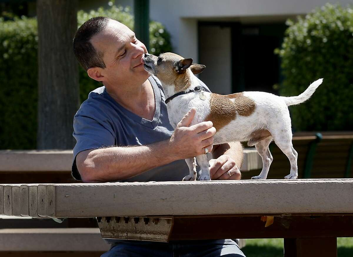 On a bench in a Brisbane park, Peter McGurty and his pup Riot enjoy each others company. Peter McGurty walks his dog Riot at a park in Brisbane, Calif. Riot had a major operation after a stone blocked his urinary tract. A group of vets have formed SF Aid for Animals, which disperses grants to pet owners who may have a financial hardships .