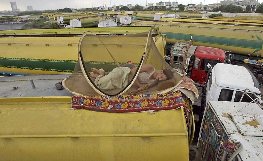 A Pakistani man sleeps on top of  an oil tanker, which was used to transport NATO fuel supplies to Afghanistan, while parked with other tankers in Karachi, Pakistan, Tuesday, July 3, 2012. The Obama administration said Tuesday that Pakistan was reopening its supply lines into Afghanistan, after the U.S. belatedly issued an apology for the November killing of 24 Pakistani troops in a NATO airstrike. (AP Photo/Fareed Khan) Photo: Fareed Khan, Associated Press