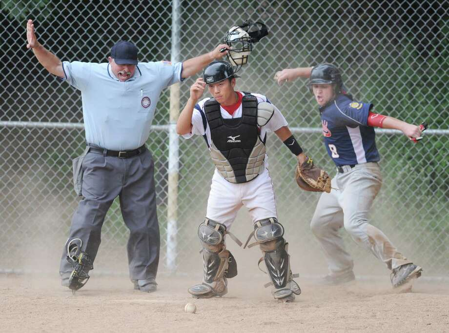 Collin O'Meara, right, # 8 of Ridgefield, reacts to being called safe by the umpire as Greenwich catcher Ricky Okazaki, center, searches for the ball during a play at the plate in the top of the second inning in Senior American Legion baseball game between Ridgefield and Greenwich at Julian Curtiss School in Greenwich, Tuesday, July, 3, 2012. Photo: Bob Luckey / Greenwich Time