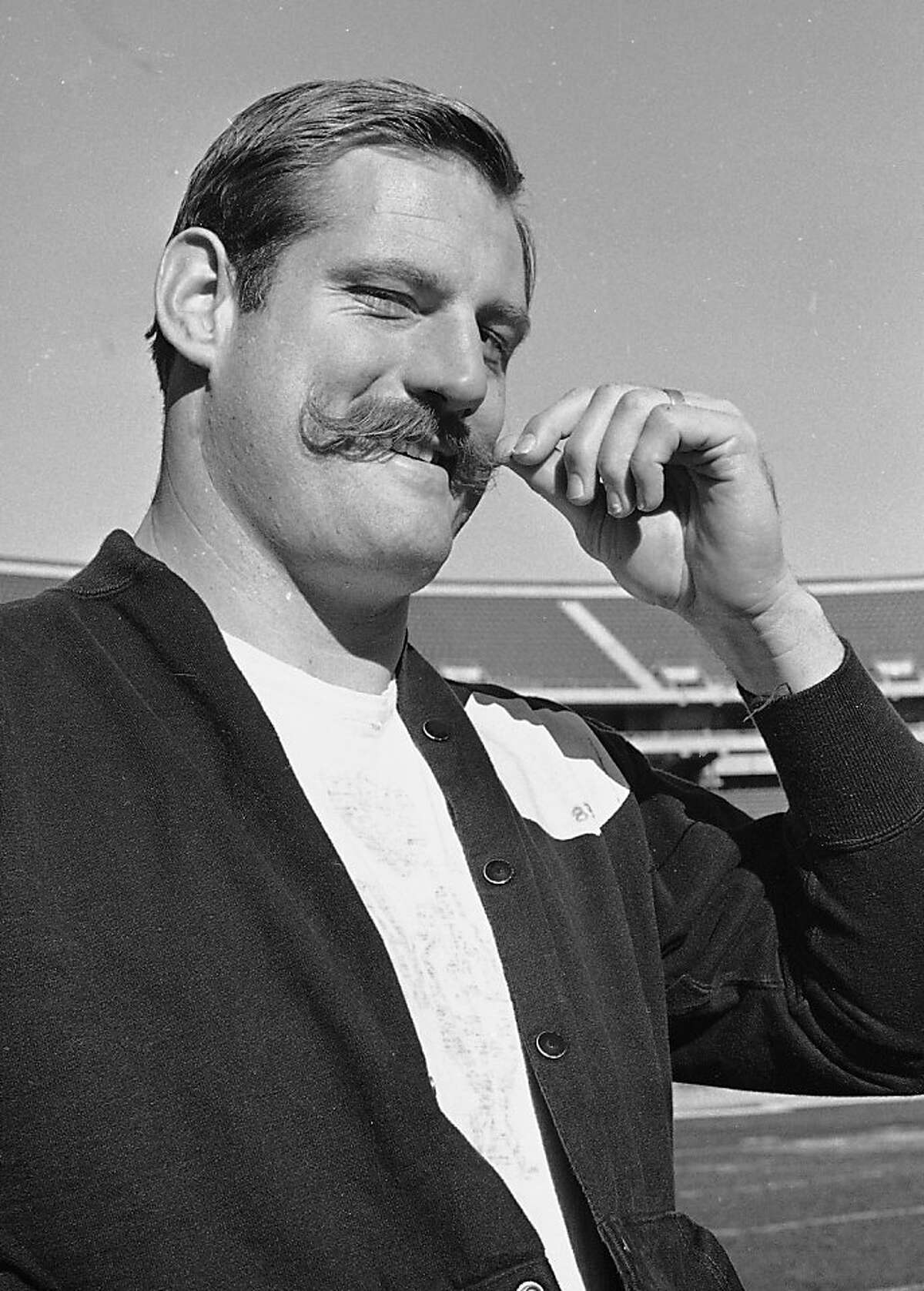 FILE - In this Jan. 3, 1968, file photo, Oakland Raiders defensive end Ben Davidson twirls his handlebar moustache in Oakland, Calif., as he contemplated the coming meeting with the Green Bay Packers in the NFL championship game. Davidson, the hulking defensive end who starred for the Raiders in the 1960s before becoming a famous television pitch man, died Monday night, July 2, 2012. He was 72. (AP Photo/Ernest Bennett)