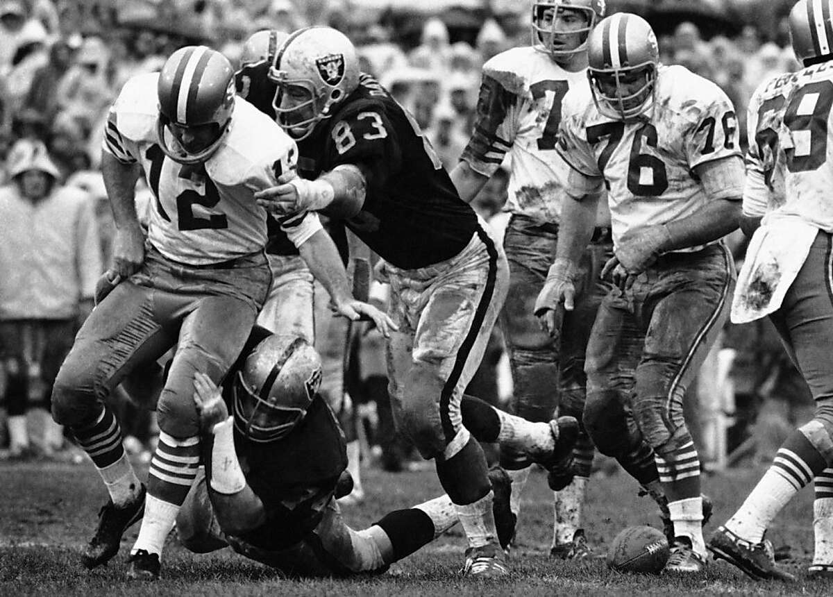 FILE - In this Dec. 20, 1970, file photo, Oakland Raiders' Ben Davidson (83) and Tom Keating, on ground, get to San Francisco 49ers quarterback John Brodie during an NFL football game in Oakland, Calif. The play was called back and San Francisco was penalized for illegal procedure. Davidson, the hulking defensive end who starred for the Raiders in the 1960s before becoming a famous television pitch man, died Monday, July 2, 2012. He was 72. (AP Photo/File)