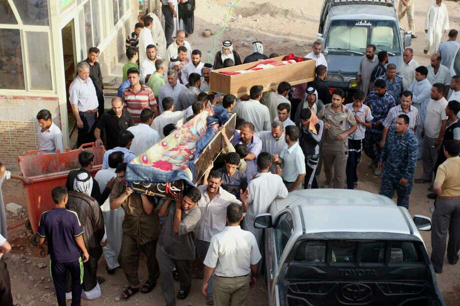 Victims are taken for burial in Najaf, 100 miles south of Baghdad, in the aftermath of bombing attacks that may have been aided by bribed guards. Photo: Alaa Al-Marjani / AP