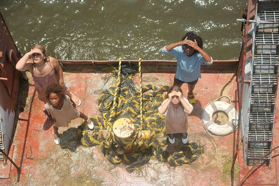 """Quvenzhane Wallis as """"Hushpuppy""""  and the bathtub girls on Sargeant Major's boat on the set of BEASTS OF THE SOUTHERN WILD. Photo: Jess Pinkham, Fox Searchlight"""