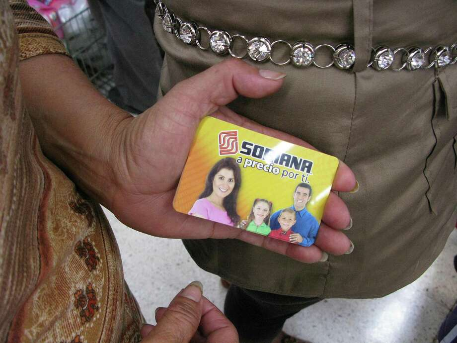 A woman shows her pre-paid gift card while waiting at a Soriana supermarket in Mexico City July 3, 2012. Some cardholders didn't get as much as promised or their cards weren't working. Photo: Marco Ugarte / AP