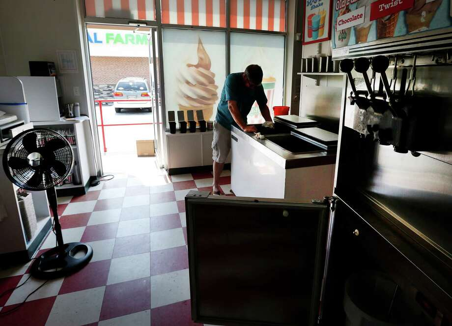 Tom Morgan cleans an empty ice cream freezer in his store in Towson, Md., Tuesday, July 3, 2012, as he waits for power to return for the first time since last weekend's severe storms. (AP Photo/Patrick Semansky) Photo: Patrick Semansky / AP