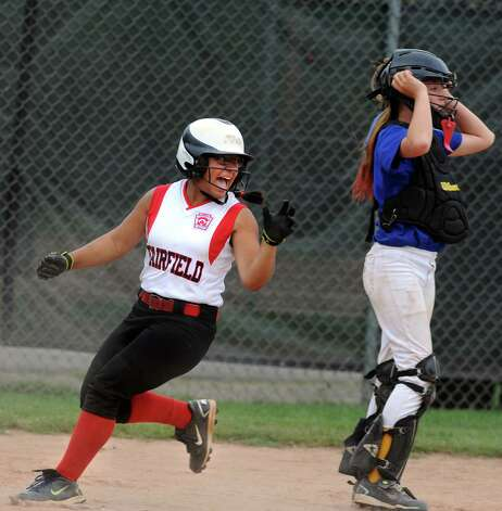 Fairfield's Brittany Romero crosses home plate tying the score in the fifth inning as Black Rock catcher Gigi Spear looks on during the District 2 Little League softball championship Tuesday, July 3, 2012 at Unity Park in Trumbull, Conn. Photo: Autumn Driscoll / Connecticut Post