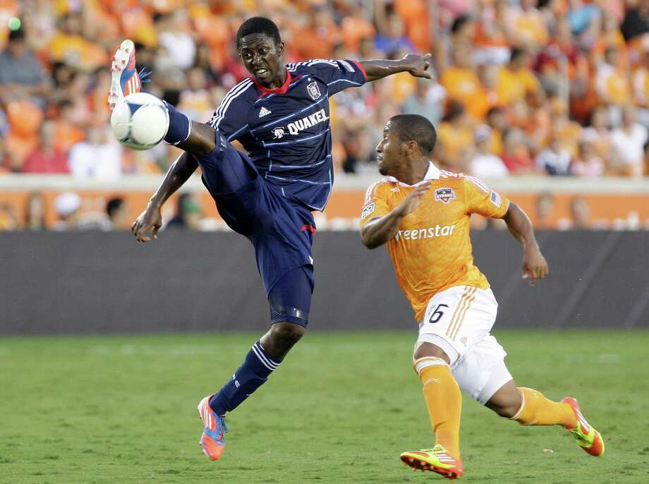 Chicago Fire forward Patrick Nyarko (14) kicks the ball away from Houston Dynamo midfielder Corey Ashe. Photo: Thomas B. Shea, For The Chronicle / © 2012 Thomas B. Shea