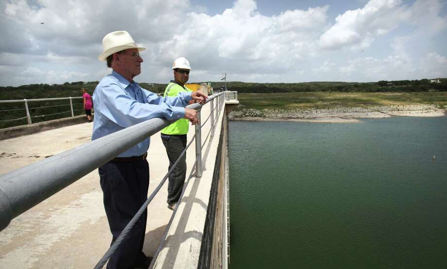 Bexar County Judge Nelson Wolff, left, and Jason Ochoa of Austin Bridge and Road, look out over Medina Lake from the top of the dam which is being reinforced, Monday, July 2, 2012. Photo: BOB OWEN, San Antonio Express-News / © 2012 San Antonio Express-News