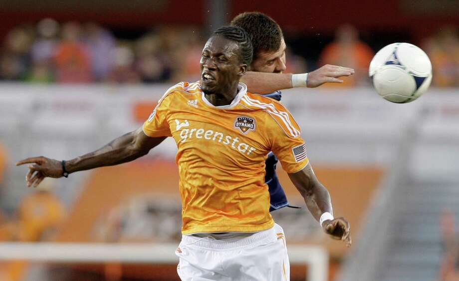 7/3/12: Houston Dynamo midfielder/forward Macoumba Kandji (9) heads the ball from Chicago Fire defender Gonzalo Segares (13) at BBVA Compass Stadium in Houston, Texas. Photo: Thomas B. Shea, For The Chronicle / © 2012 Thomas B. Shea