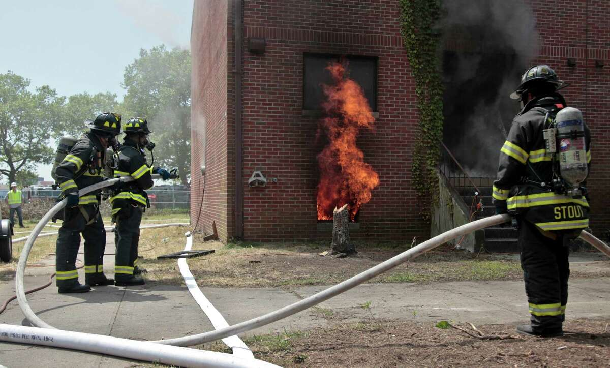 Firefighters prepare to fight a controlled blaze in a vacant building on Governors Island as part of research aimed at obtaining important data on fire behavior on Tuesday, July 3, 2012 in New York. An electronic switch ignited a match on a sofa in the decommissioned Coast Guard row house for a
