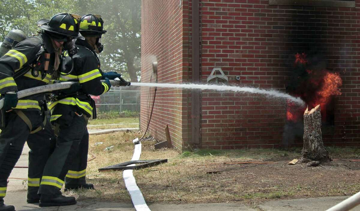Firefighters spray water onto a controlled blaze in a vacant building on Governors Island as part of research aimed at obtaining important data on fire behavior on Tuesday, July 3, 2012 in New York. An electronic switch ignited a match on a sofa in the decommissioned Coast Guard row house for a