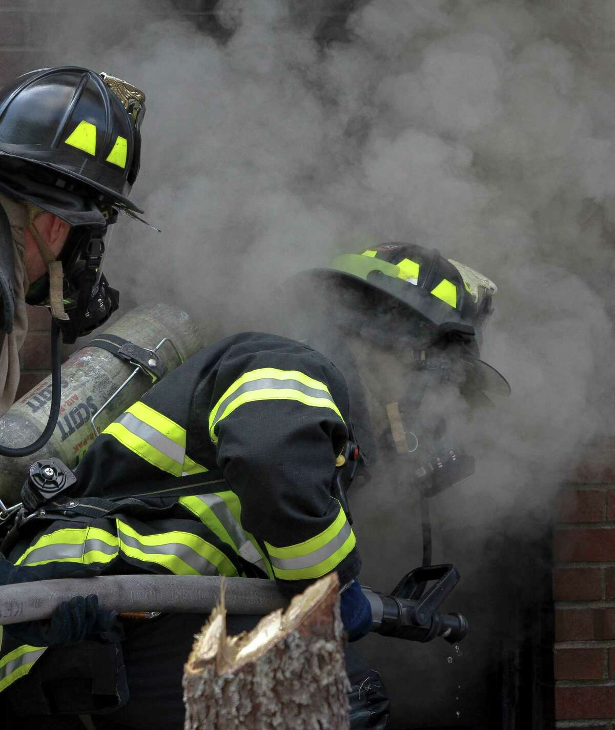 Firefighters face a smoky cellar while fighting a controlled blaze, set in a vacant building on Governors Island as part of research aimed at obtaining important data on fire behavior on Tuesday, July 3, 2012 in New York. An electronic switch ignited a match on a sofa in the decommissioned Coast Guard row house for a