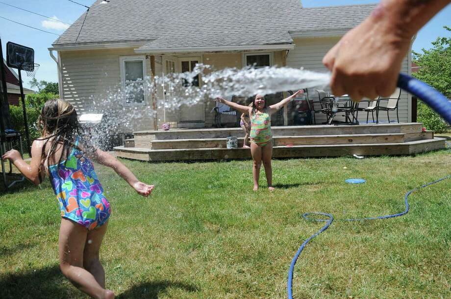 Danielle, left, 5, and Mattia, 8, get cooled down as their great aunt Leslie Heermance sprays them with a hose on Tuesday, July 3, 2012 in Rotterdam, NY.  Heermance said she was unaware of the town's water conservation measure that was in place.  (Paul Buckowski / Times Union) Photo: Paul Buckowski