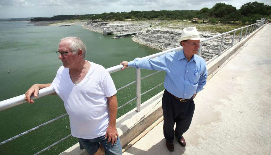 Bexar County Judge Nelson Wolff, right, and Philip Brant stand on top of Medina Lake Dam.  The dam is the only way for Brant to get to his house.  Monday, July 2, 2012. Photo: BOB OWEN, San Antonio Express-News / © 2012 San Antonio Express-News