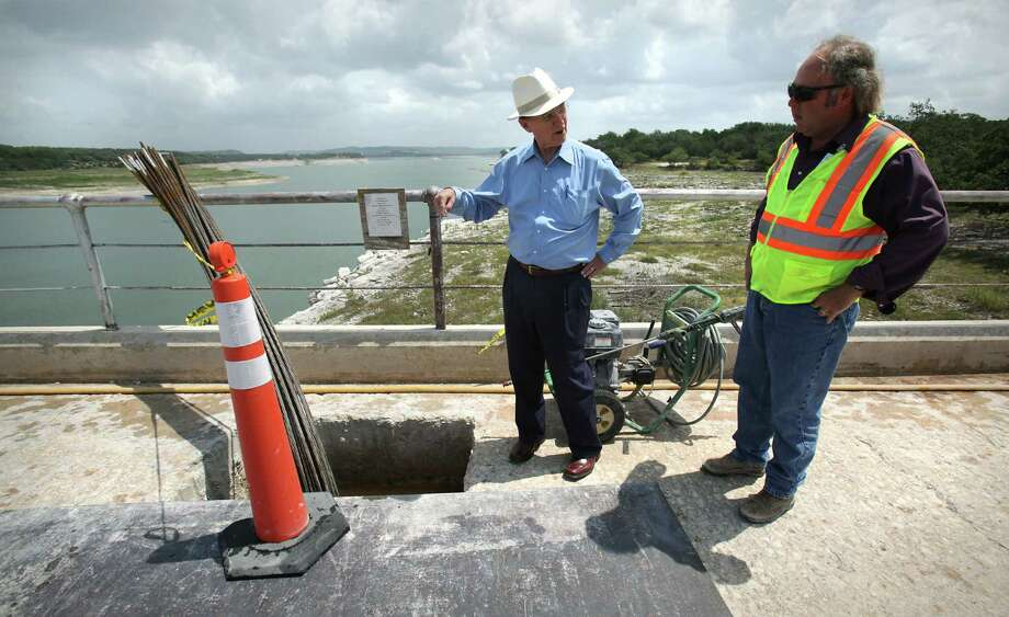 "Bexar County Judge Nelson Wolff, left, asks Kris Roberson, Senior Engineering Technician for San Antonio River Authority, about the ""anchors"" installed at the construction project at the Medina Lake Dam which is reinforcing the structure, Monday, July 2, 2012. Photo: BOB OWEN, San Antonio Express-News / © 2012 San Antonio Express-News"