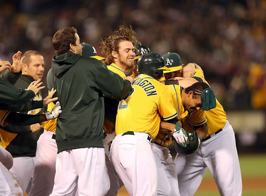 OAKLAND, CA - JULY 03:  Coco Crisp #4 of the Oakland Athletics is congratulated by teammates after he hit a sacrifice fly that scored Cliff Pennington #2 to beat the Boston Red Sox in the ninth inning at O.co Coliseum on July 3, 2012 in Oakland, California.  (Photo by Ezra Shaw/Getty Images) Photo: Ezra Shaw, Getty Images