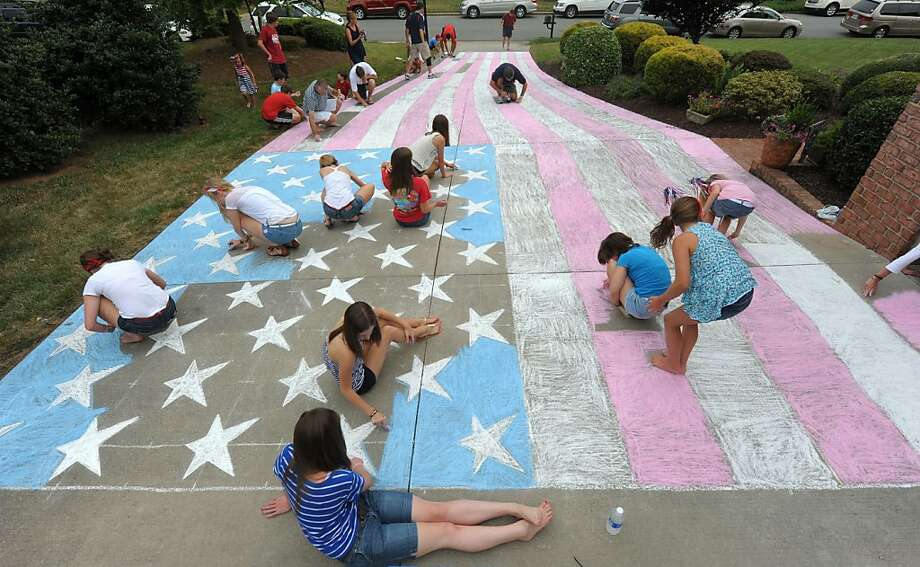 People participate in the annual Piatt Sidewalk Chalk American Flag Project celebrating Independence Day at the Piatt's house in Elon, N.C. Tuesday, July 3, 2012. (AP Photo/Burlington Times-News, Sam Roberts) Photo: Sam Roberts, Associated Press