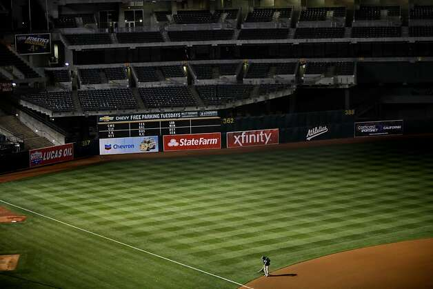 A groundskeeper touches up the field as the lights are turned off after the Oakland A's game against the Blue Jays in Oakland, Calif., Tuesday, May 8, 2012. Photo: Sarah Rice, Special To The Chronicle