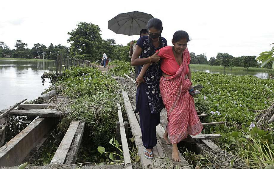 Indian villagers cross a broken bridge at flood affected Phateki, 270 kilometers (169 miles) east of Gauhati, India, Tuesday, July 3, 2012. Nearly half a million people took refuge in relief camps set up in government buildings after the devastating floods killed 95 people and left 14 missing in northeastern Assam state. (AP Photo/Anupam Nath) Photo: Anupam Nath, Associated Press