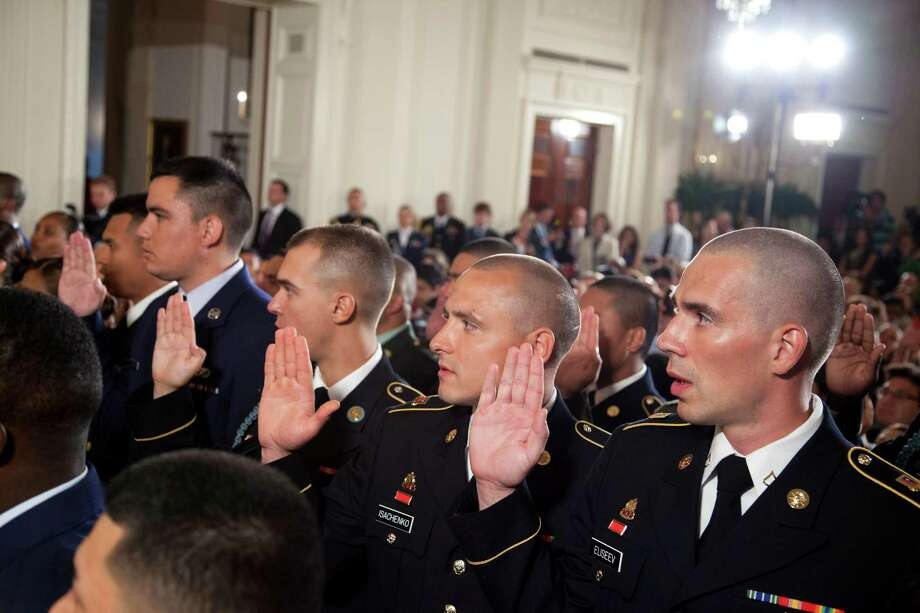 Service members take part in a naturalization ceremony in the East Room of the White House with President Barack Obama, Wednesday, July 4, 2012, in Washington.  (AP Photo/Evan Vucci) Photo: Evan Vucci, Associated Press / AP