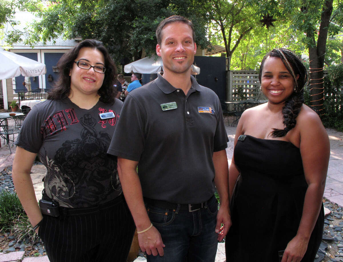 Board member Jezzika Lee Perez, from left, president Chad Nall and board member Tonya Perkins gather at the Lesbian, Gay, Bisexual and Transgender Chamber of Commerce mixer at the Candlelight Coffee House.