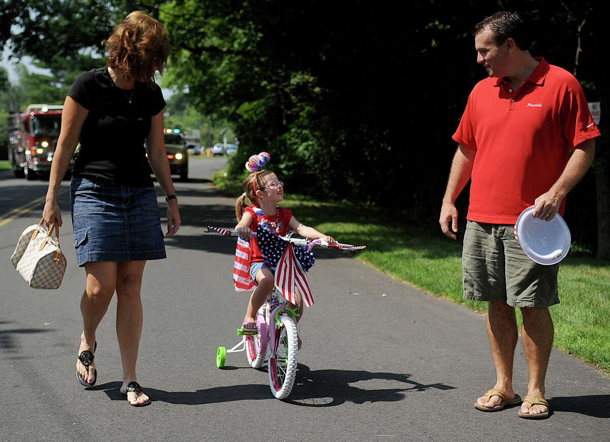 Michaela O'Brien, 3, brings up the rear during Wednesday's YWCA Push-n-Pull Parade in Darien on July 4, 2012.