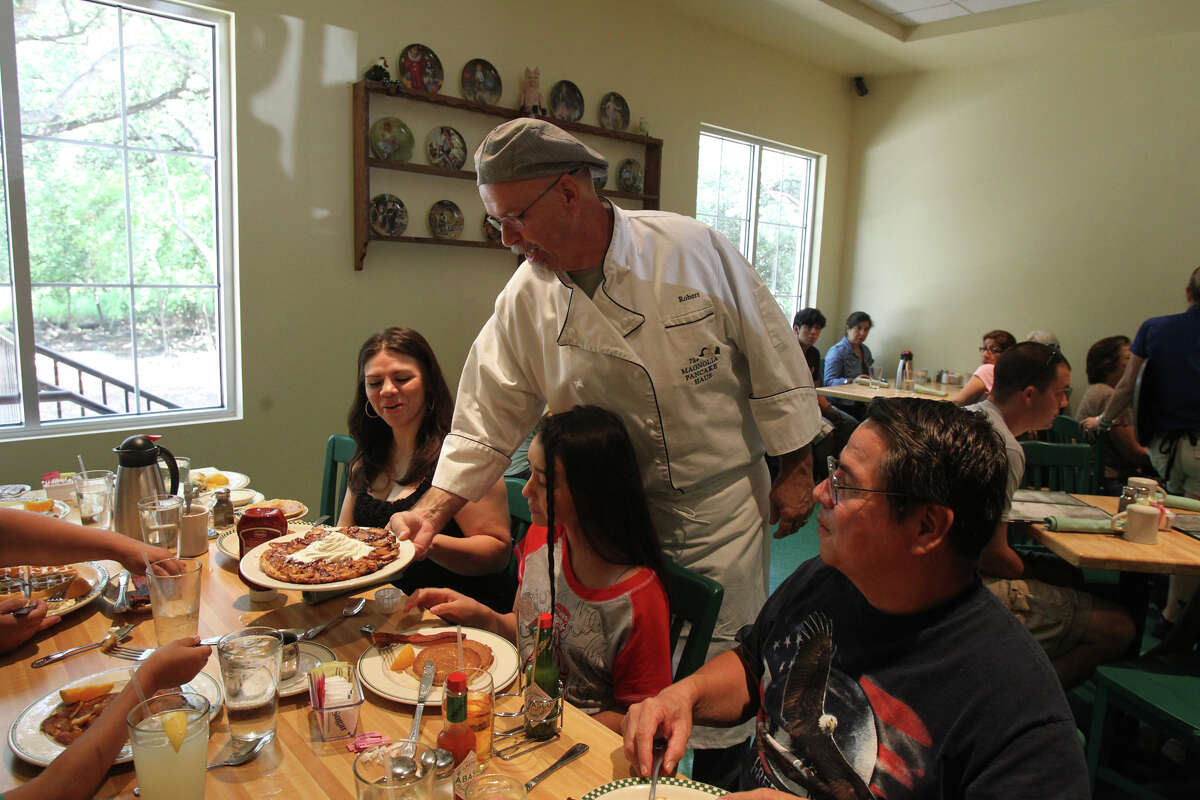 Robert Fleming, (standing in white outfit) owner of the Magnolia Pancake Haus, serves up a specialty item to customers Monica Garza (left), Deanna Zavala,11, and Alex Garza (right). The restaurant now has a second location on Huebner road. John Davenport/San Antonio Express-News