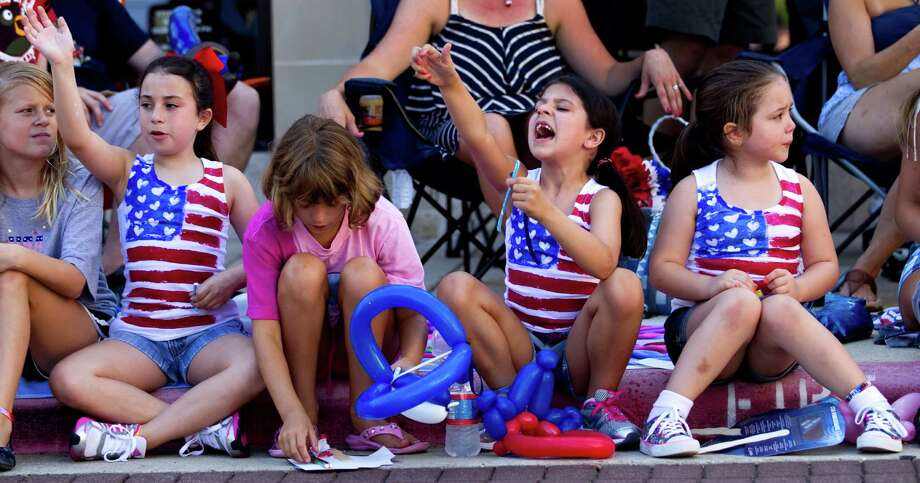 Zoe Luckett, far left, Hannah Wilhelm, Kate Luckett and Maya Shahmansocrian, far right, sit on the sidewalk as they watch the annual Fourth of July Parade at Market Street Wednesday, July 4, 2012, in The Woodlands. Photo: Brett Coomer, Houston Chronicle / © 2012 Houston Chronicle