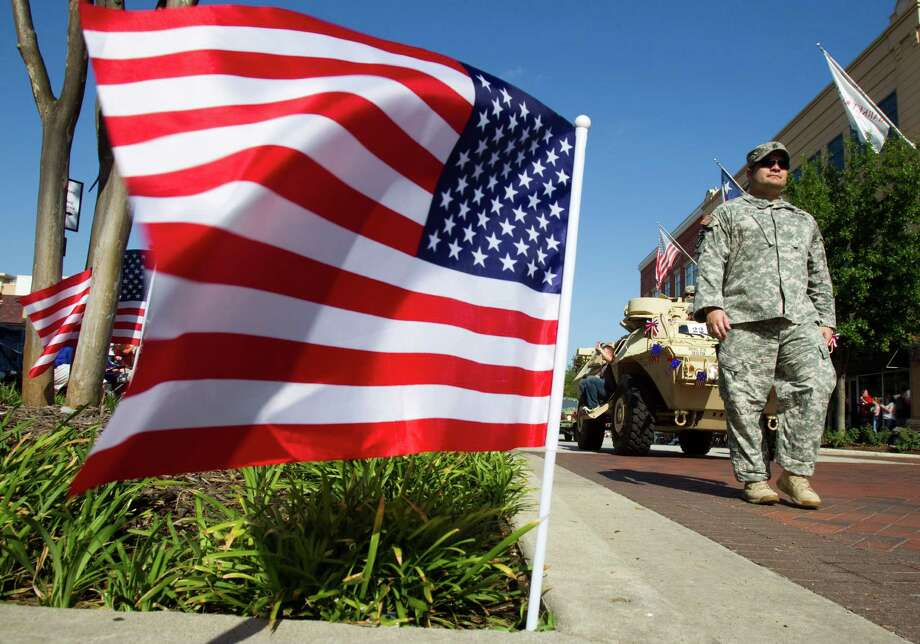 A flag waves along with parade route as U.S. Army soldiers march by during the annual Fourth of July Parade at Market Street Wednesday, July 4, 2012, in The Woodlands. Photo: Brett Coomer, Houston Chronicle / © 2012 Houston Chronicle