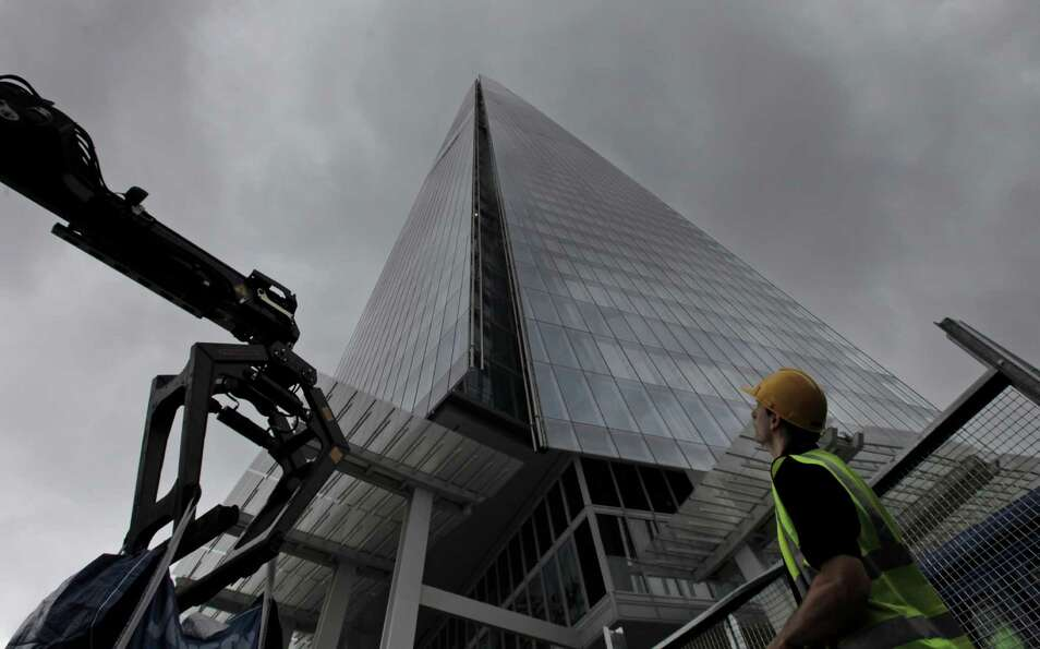 A worker looks up at the Shard, a newly-constructed high-rise building that is western Europe's ta