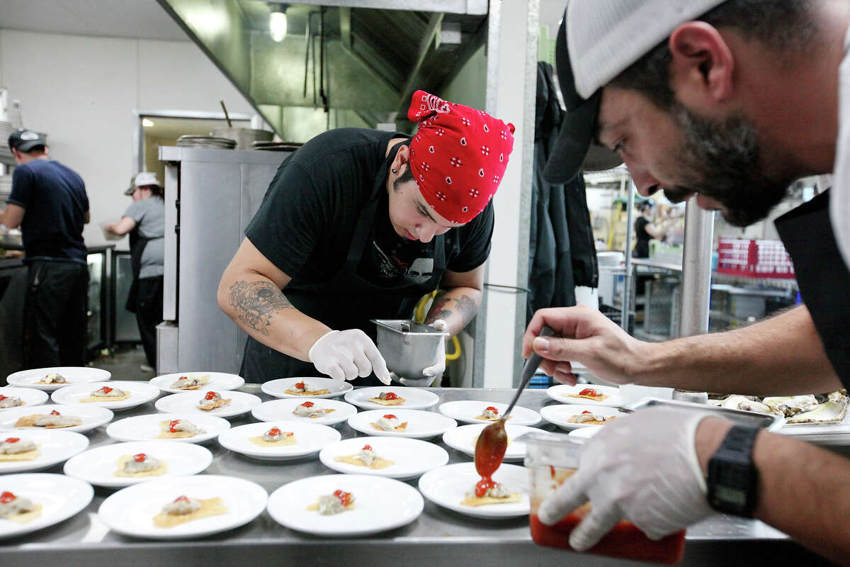 Cody Orozco, a former chef at Knife & Fork Gastropub, (left) and his brother Javier Orozco, executive chef and owner, plate oysters during the 2012 Nose-to-Tail dinner by Texas Cooks Co-Op. The restaurant will appear on Food Network's