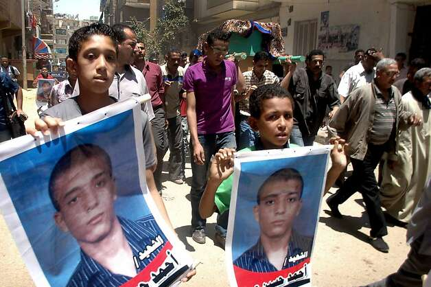 Egyptian boys hold posters of Ahmed Hussein Eid who was fatally stabbed by three bearded men during his funeral procession in the city of Suez, Egypt, Wednesday, July 4, 2012. The murder of a university student by suspected militants as his girlfriend looked on is fueling fears in Egypt that vigilante groups seeking to enforce a strict interpretation of Islam's teachings may be feeling confident with an Islamist president in office to take over the streets. (AP Photo) Photo: Str, Associated Press