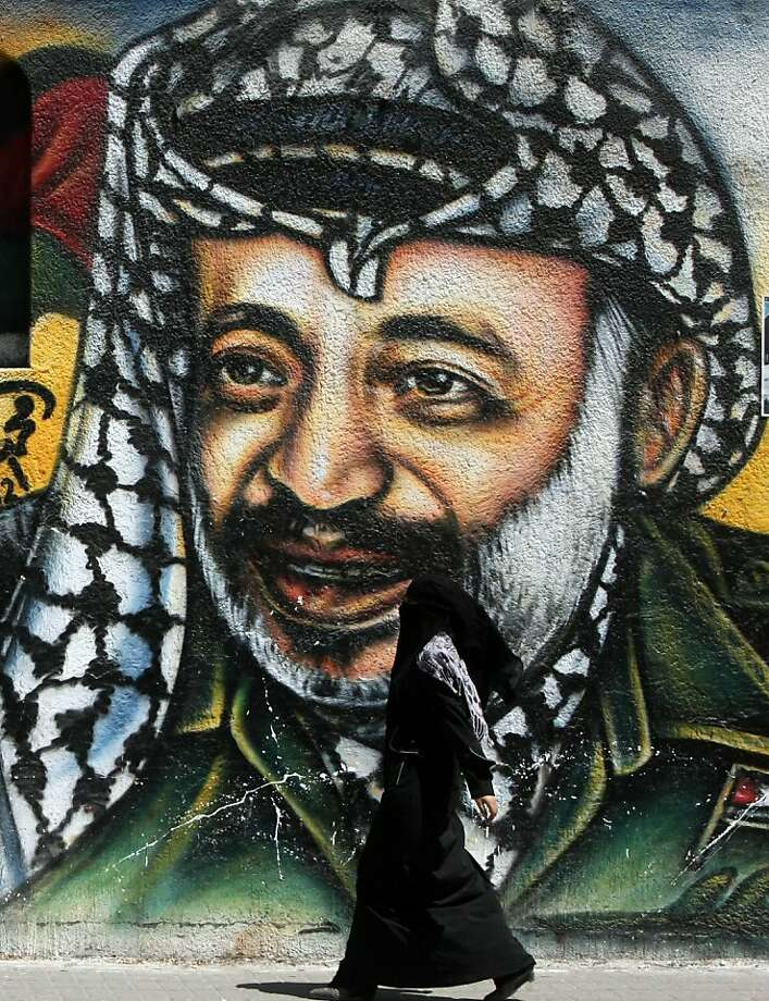 A Palestinian woman walks past a mural of late Palestinian leader Yasser Arafat in Gaza City on July 4, 2012. Arafat, who died in 2004, was poisoned by polonium, according to the findings of laboratory research carried out in Switzerland and cited in an Al-Jazeera report on July 3. Photo: Mahmud Hams, AFP/Getty Images