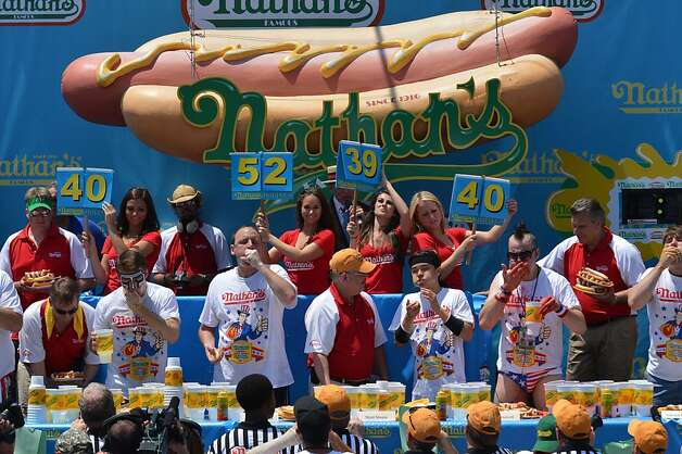 Men compete during Nathan's Famous Fourth of July International Hot Dog Eating Contest July 4, 2012 in the Coney Island section of New York.Five-time Nathan's Famous Champion Joey Chestnut won his sixth title by equaling his record of 68 hot dogs and buns in ten minutes. Photo: Stan Honda, AFP/Getty Images