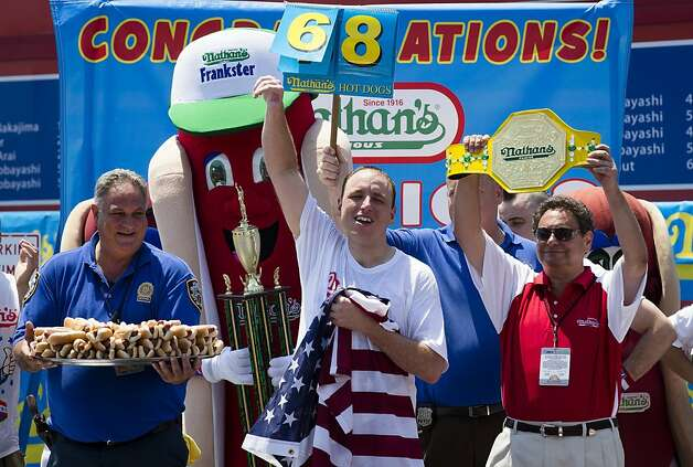 Five-time reigning champion Joey Chestnut celebrates after he wins his sixth straight Coney Island hot dog eating contest on Wednesday, July 4, 2012  at Coney Island, in the Brooklyn borough of New York. Chestnut tied his personal best and the record with eating 68 hot dogs. Last year, Chestnut won with 62 hot dogs Photo: John Minchillo, Associated Press