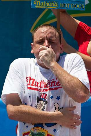 NEW YORK, NY - JULY 04:  Competitive eater Joey Chestnut competes in the Nathan's Famous International Hot Dog Eating Contest at Coney Island on July 4, 2012 in the Brooklyn borough of New York City. Chestnut won the men's division by successfully tying his own world record by eating 68 hot dogs in 10 minutes.  (Photo by Andrew Burton/Getty Images) Photo: Andrew Burton, Getty Images