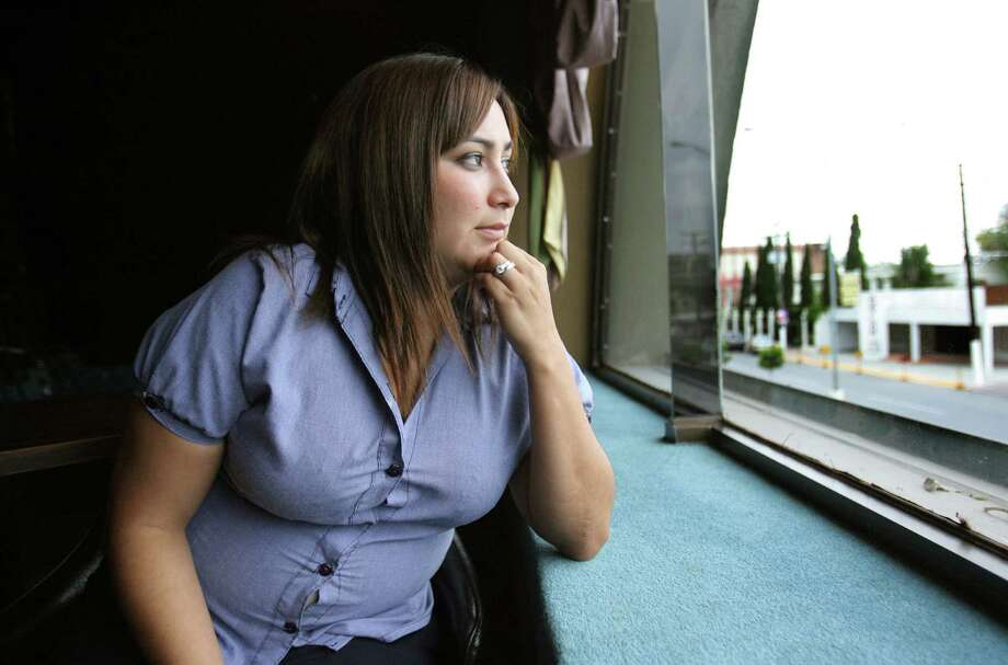 Brenda Vazquez,29, an elementary school teacher in Matamoros, Mexico, looks from a window in a building along Avenida Alvaro Obregon recently. Vazquez was delivered by a midwife  in south Texas, but pressured by U.S. Border Patrol agents to deny their U.S. citizenship. Vasquez was born in Weslaco, Texas.  SPECIAL TO THE EXPRESS NEWS/ PHOTO BY DELCIA LOPEZ Photo: Delcia Lopez, SPECIAL TO THE EXPRESS NEWS