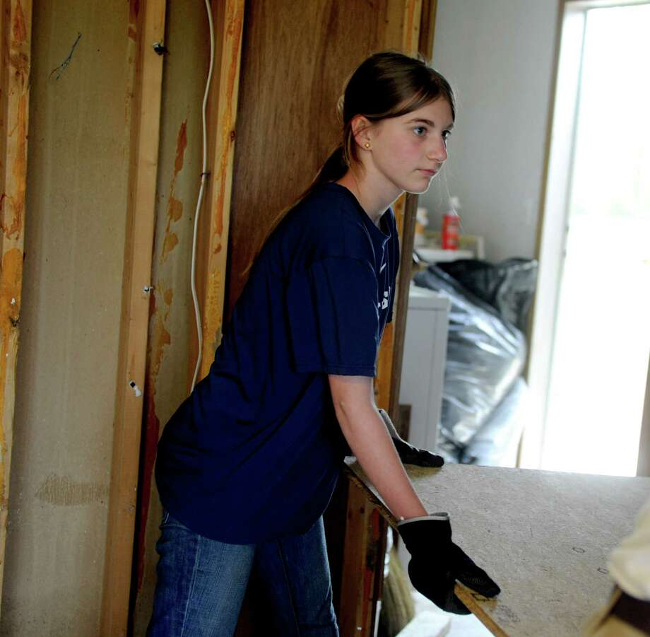 In an April 19, 2012 photo, Logan Etheredge, 12, of Darien, Conn. helps make repairs to this tornado damaged home in Gadsden, Ala. Instead of basking in the sun on a beach in Hawaii earlier this month during her spring break, Etheredge spent a week with her family rebuilding houses in DeKalb County damaged by the April 27, 2011, tornadoes.  (AP Photo/Gadsden Times, Sarah Dudik) Photo: Sarah Dudik, AP / Gadsden Times