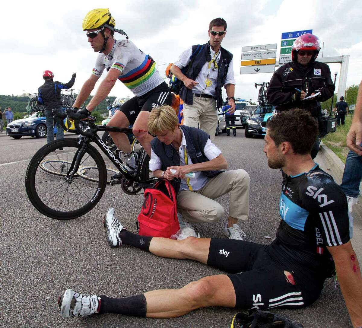 Mark Cavendish of Britain gets back on his bike after crashing with teammate Bernhard Eisel (right) of Austria during the fourth stage of the Tour de France.